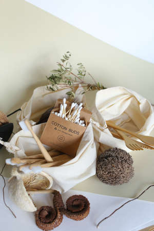 Wooden spoons and fork, bamboo toothbrushes, cotton buds in tissue white pouches. Concept of ecofriendly