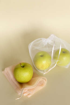 Green non gmo apples in reusable eco friendly ecological transparent bags on bright background with copy space.