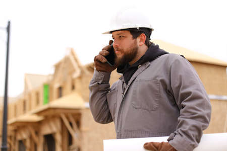 Caucasian builder talking by mobile phone and holding drawing plan at construction site, wearing hardhat. Concept of architectural profession and house building.