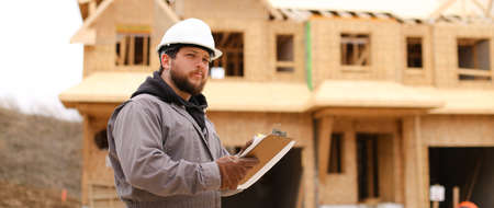 Banner of engineer drawing plan in notebook at construction site and wearing hardhat. Concept of architectural profession and house building.