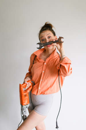 Young woman holding a drill and kissing wrench, wearing orange shirt standing on isolated background. Concept of repairs tools and attractive wife.