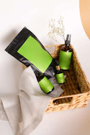 Black doy pack and spray bottles  cosmetic products in wicker basket, green space for your brand. Banco de Imagens