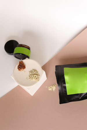 Black doy pack and jar cosmetic products and green space for your brand, clay powder on white plate.