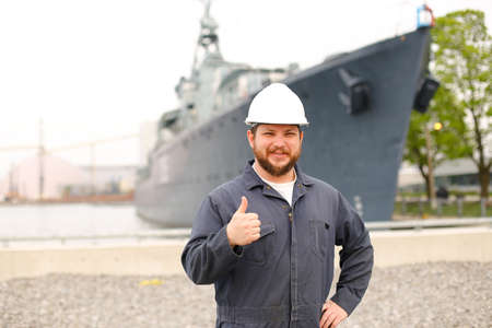 Portrait of marine captain standing near big vessel in background, showing thumbs up and wearing helmet with work jumpsuit. Concept of maritime job and profession, marine team.