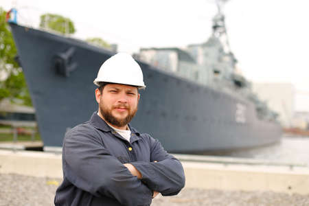 Portrait of marine chief mate standing near big vessel in background and wearing helmet with work jumpsuit. Concept of maritime job and profession, marine team.