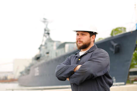 Portrait of marine chief officer standing near big vessel in background and wearing helmet with work jumpsuit. Concept of maritime job and profession, marine team.
