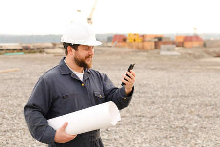 American building enginer holding VHF walkie talkie and blueprints papers on construction site, wearing helmet and work jumpsuit. Concept of builder profession.