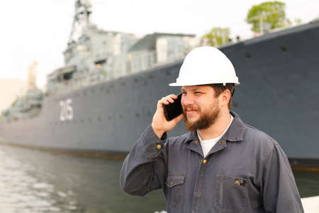 Marine deck officer speaking by VHF walkie talkie near vessel in background, wearing helmet and work jumpsuit. Concept of maritime profession , job and seaman.