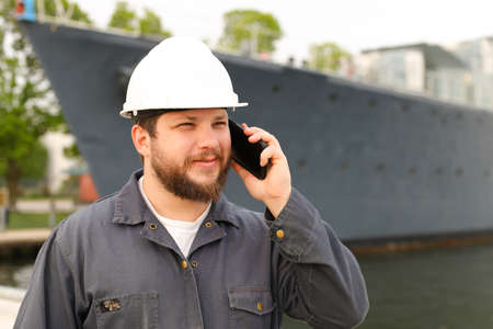 Marine first mate speaking by VHF walkie talkie near vessel in background, wearing helmet and work jumpsuit. Concept of maritime profession , job and seaman.