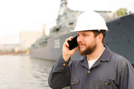 Marine engineer speaking by VHF walkie talkie near vessel in background, wearing helmet and work jumpsuit. Concept of maritime profession , job and seaman.
