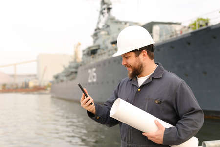 Marine DDE, designated duty engineer, speaking by VHF walkie talkie, holding blueprints near vessel in background, wearing helmet and work jumpsuit. Concept of maritime profession , job and seaman.