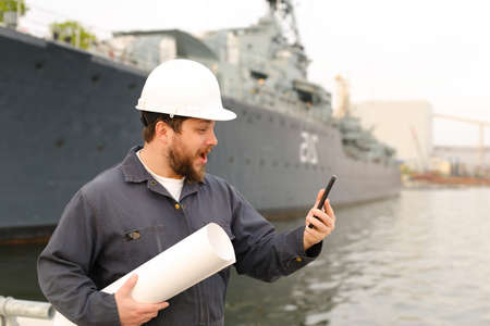 Marine engineer holding VHF walkie talkie and blueprints near vessel in background, wearing helmet and work jumpsuit. Concept of maritime profession , job and seaman.