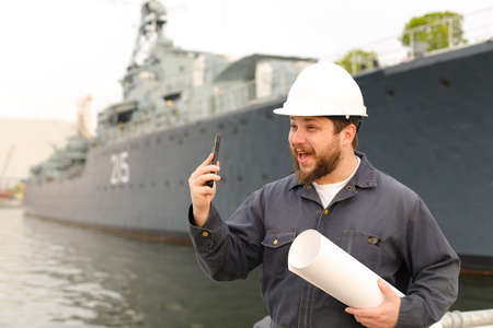 Marine assistant engineer holding VHF walkie talkie and blueprints near vessel in background, wearing helmet and work jumpsuit. Concept of maritime profession , job and seaman. Reklamní fotografie