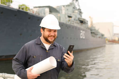 Marine smiling engineer speaking by VHF walkie talkie, holding blueprints near vessel in background, wearing helmet and work jumpsuit. Concept of maritime profession , job and seaman.