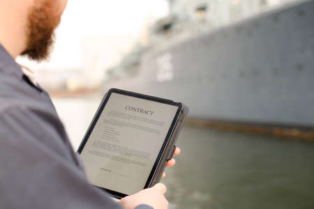 Marine engineer reading contract on electronic book or tablet near vessel in background. Concept of maritime profession and mpdern technology.