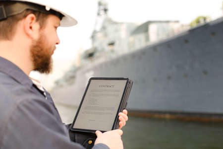 First mate reading contract on electronic book or tablet near vessel in background. Concept of maritime profession and modern technology.