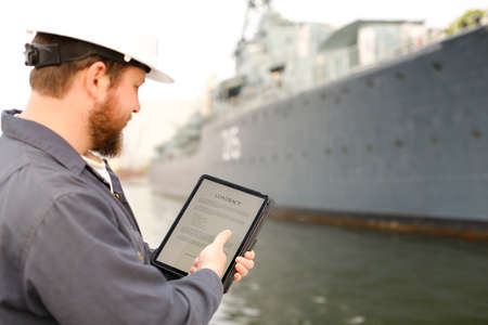 Captain in helmet reading contract on electronic book or tablet near vessel in background. Concept of maritime profession and modern technology.