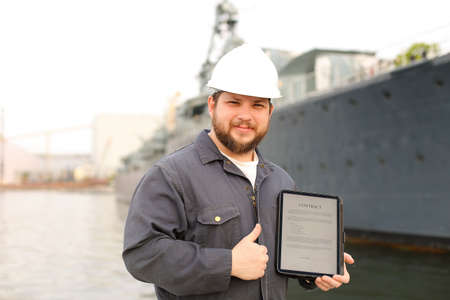 Captain in helmet reading contract on electronic book or tablet and showing thumbs up near vessel in background. Concept of maritime profession and modern technology.