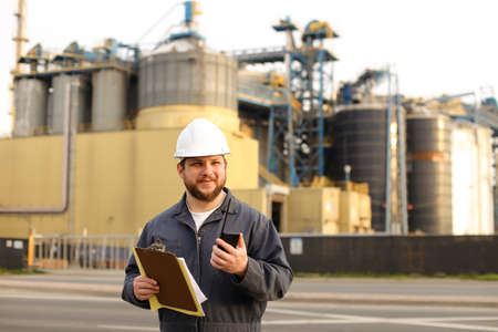 Engineer holding VHF walkie talkie and notes, factory in background. Man wearing helmet and work jumpsuit. Concept of engineering profession and modern technology, worker. Stock Photo
