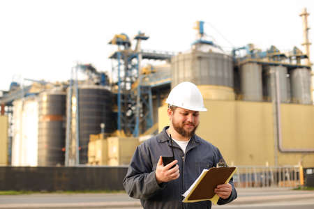 Male engineer holding VHF walkie talkie and notes, factory in background. Man wearing helmet and work jumpsuit. Concept of engineering profession and modern technology, worker.