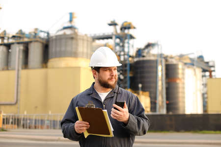 Caucasian engineer holding VHF walkie talkie and notes, factory in background. Man wearing helmet and work jumpsuit. Concept of engineering profession and modern technology, worker.