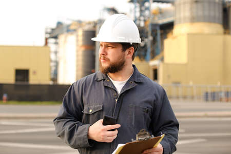 Portrait of engineer holding VHF walkie talkie and notes, factory in background. Man wearing helmet and work jumpsuit. Concept of engineering profession and modern technology, worker.