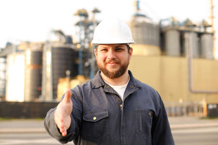 Portrait of male industrial worker with outstretched hand standing near factory. Man wearing white helmet and blue work jumpsuit. Concept of plant engineering profession.