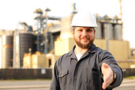 Portrait of male caucasian industrial worker with outstretched hand standing near factory. Man wearing white helmet and blue work jumpsuit. Concept of plant engineering profession.