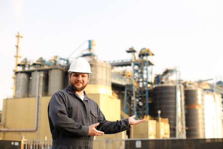 Portrait of male industrial worker and engineer showing factory exterior outdoors. Man wearing white helmet and blue work jumsuit. Concept of plant jobs, engineering profession. Banco de Imagens