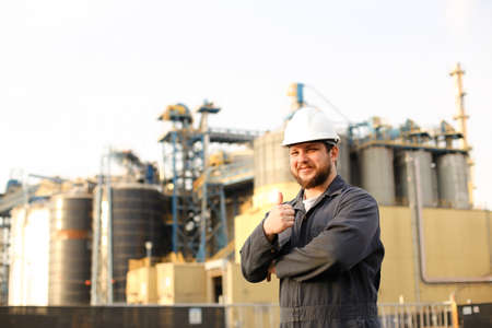 Portrait of male industrial worker showing thumbs up factory outdoors. Man wearing white helmet and blue work jumsuit. Concept of plant jobs, engineering profession.
