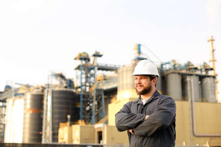Portrait of male industrial worker standing near factory outdoors. Man wearing white helmet and blue work jumsuit. Concept of plant jobs, engineering profession. Banco de Imagens
