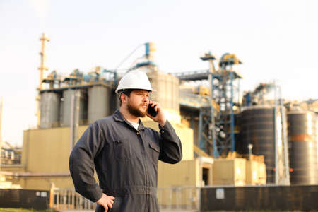 Industrial worker speaking by VHF walkie talkie near factory outside. Man wearing white helmet and blue work jumpsuit. Concept of modern technology, plant engineering jobs. Banco de Imagens