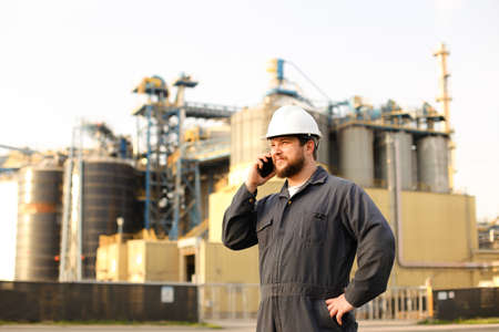 Industrial director speaking by VHF walkie talkie near factory outside. Man wearing white helmet and blue work jumpsuit. Concept of modern technology, plant engineering jobs.