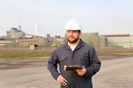 Portrait of male engineer standing on construction site and holding papers. Man wearing white helmet and work jumpsuit. Concept of industry profession and building engineering job.
