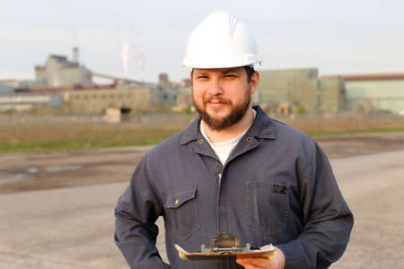 Portrait of american engineer standing on construction site and holding papers. Man wearing white helmet and work jumpsuit. Concept of industry profession and building engineering job.