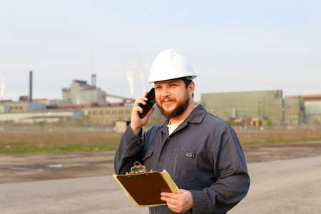 Portrait of foreman speaking by walkie talkie on construction site and holding papers. Man wearing white helmet and work jumpsuit. Concept of industry profession and building engineering job.