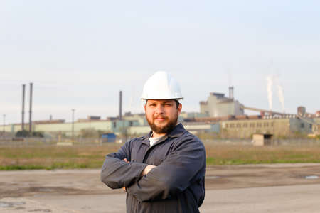 Portrait of caucasian foreman in white helmet standing in construction site background. Concept of engineering profession and industrial development. Reklamní fotografie
