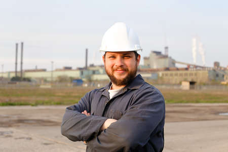 Portrait of caucasian engineer in white helmet standing in construction site background. Concept of engineering profession and industrial development.