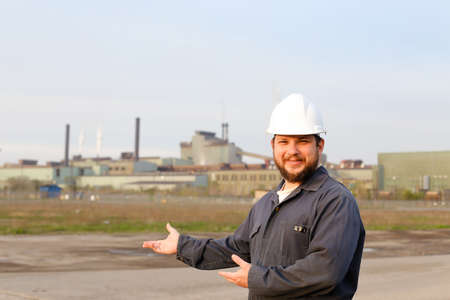 Portrait of caucasian male foreman in white helmet standing in construction site background. Concept of engineering profession and industrial development.