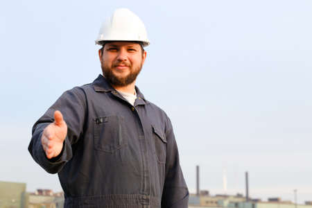 Portrait of european foreman in helmet with outstetched hands standing in construction site background. Concept of engineering profession and industrial development. Reklamní fotografie