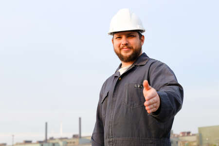 Portrait of male foreman in helmet with outstetched hands standing in construction site background. Concept of engineering profession and industrial development. Reklamní fotografie