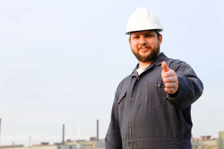 Portrait of american foreman in helmet with thumbs up standing in construction site background. Concept of engineering profession and industrial development. Reklamní fotografie