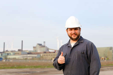 Portrait of american foreman in helmet with thumbs up standing in construction site background. Concept of engineering profession and industrial development. Banco de Imagens