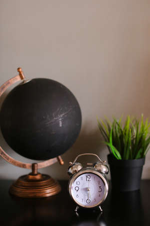 Black globe and clock standing on table near houseplant.