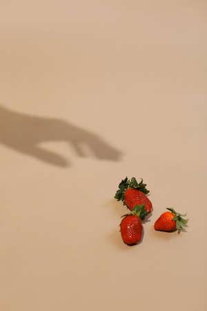 fresh stawberry with hand shadow. healthy vitamins eating