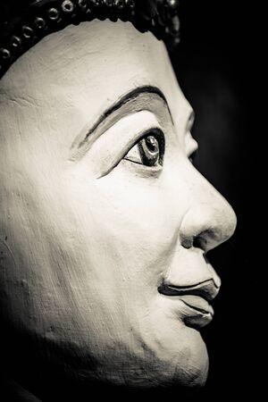 head wise: Buddha portrait isolated on black; monochrome