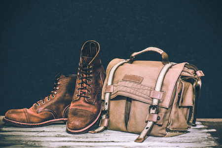 mens fashion: Mens boots and brown bag on wooden table Stock Photo
