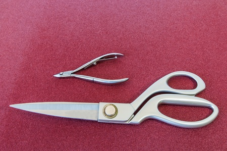 Skin and fabric cutting scissors on red background  Stock Photo - 16255192