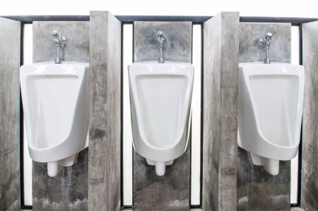 Urinals in male toilets made   of white porcelain in a row  photo
