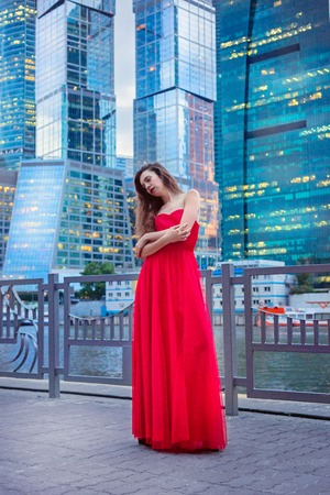 standby: The girl in the red dress on the background of skyscrapers . standby Concept Stock Photo